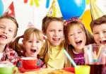 Children at a party with balloons and party food